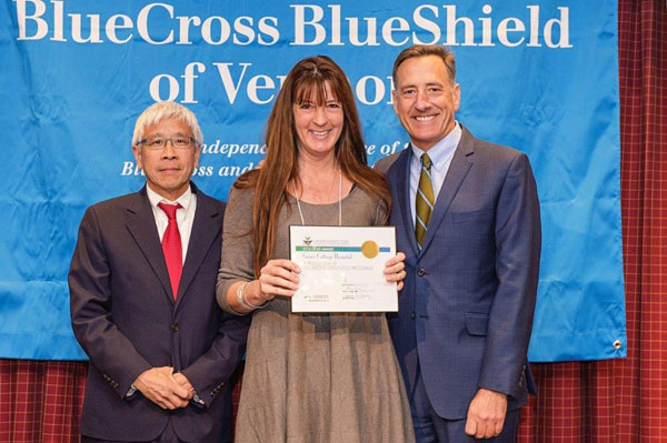 Grace Cottage Hospital Wellness Director Crystal Mansfield receives a Gold Level Workplace Wellness Initiative Award from (left) Vermont Health Commissioner Harry Chen and (right) Vermont Governor Peter Shumlin.